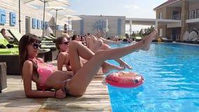 Sortee las piernas que agitan de la gente en la cámara lenta en entrenamiento cerca de piscina azul al aire libre metrajes