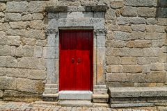 Sortelha historical mountain village, built within Medieval fortified walls, included in Portugal`s Historical village. Route. Bright red church door entrance stock photography