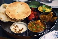 Sorterad indisk matuppsättning i magasinet, tandurihöna, naan bröd, yoghurt, traditionell curry, roti arkivbild