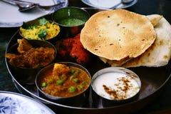 Sorterad indisk matuppsättning i magasinet, tandurihöna, naan bröd, yoghurt, traditionell curry, roti royaltyfria bilder