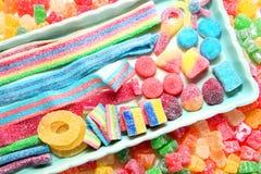 Sorterad variation av sura godisar inkluderar extrema sura tuggningar för mjuk frukt, tangenter, syrliga godisbälten och sugrör arkivbild