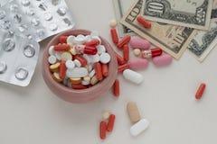 Sorterade farmaceutiska piller, tomma blåsapackar och dollarräkningar fotografering för bildbyråer