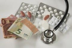 Sorterade vita piller, läkarbehandling, pengar mot vit bakgrund royaltyfri foto