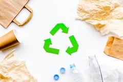 Sorterend afval en kringloop Groenboek recyclingsteken onder papierafval, plastiek, glas, polyethyleen op wit Stock Fotografie