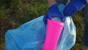 Sorterend huisvuil, milieuconcept, eindeplastiek Close-up van een vrijwilligershand die huisvuil in een groot blauw verzamelen stock videobeelden