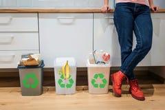 sortering av avfalls Kantjusterad sikt av färgrika avskrädefack som fylls med plast- bio mat, papper nära kvinnas ben i fotografering för bildbyråer