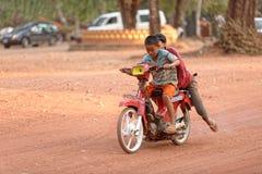 Sortes sur la motocyclette, temple de Bakong, Cambodge Photographie stock libre de droits
