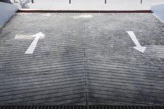 Sortez l'entrée du stationnement souterrain de voiture avec le panneau routier de flèches Images stock