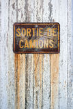 Sortie de Camions - Trucks output. Rusty sign in French with: truck exit, on a white painted wooden panel royalty free stock photo