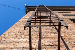 Sortie de secours rouillée sur le mur de briques rouge Photo libre de droits