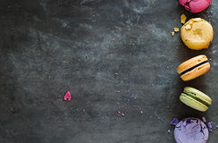 Sortierte bunte französische Makronen auf einem dunklen Steinhintergrund Stockfoto