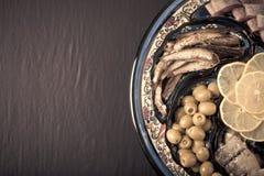 Sortierte Fische auf einer Platte auf einem dunklen Hintergrund Mit Raum für te Stockfotografie