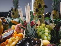 Sortierte Früchte in der Tabelle Äußere Nachtnahaufnahme Traube, Ananas, Orange, Pampelmuse, Banane, Datum lizenzfreie stockfotos