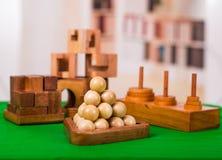 Sortierte hölzerne Gehirnharte nuss oder hölzerne Puzzlespiele auf grüner Tabelle in einem unscharfen Hintergrund Stockfotografie