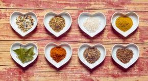 Sortierte kulinarische Gewürze in geformten Tellern des Herzens Lizenzfreie Stockfotografie