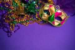 Sortierte Mardi Gras- oder Carnivale-Maske auf einem purpurroten Hintergrund Lizenzfreies Stockfoto