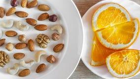 Sortierte Nüsse, orange Scheiben auf weißen Platten auf Holztisch Gesunder organischer Imbiss, Frühstück, Lebensmittelinhaltsstof lizenzfreies stockfoto