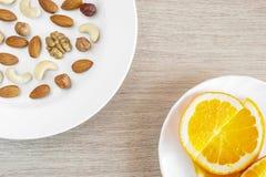 Sortierte Nüsse, orange Scheiben auf weißen Platten auf Holztisch Gesunder organischer Imbiss, Frühstück, Lebensmittelinhaltsstof lizenzfreies stockbild