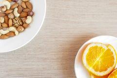 Sortierte Nüsse, orange Scheiben auf weißen Platten auf Holztisch Gesunder organischer Imbiss, Frühstück, Lebensmittelinhaltsstof stockbild