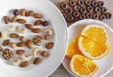 Sortierte Nüsse, orange Scheiben auf weißen Platten, knusprige ganze Korn-Getreide ringsum Hafer auf Holztisch Gesunder organisch lizenzfreie stockfotos