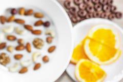 Sortierte Nüsse, orange Scheiben auf weißen Platten, knusprige ganze Korn-Getreide ringsum Hafer auf Holztisch Gesunder organisch lizenzfreie stockfotografie