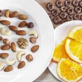 Sortierte Nüsse, orange Scheiben auf weißen Platten, knusprige ganze Korn-Getreide ringsum Hafer auf Holztisch Gesunder organisch stockfotos