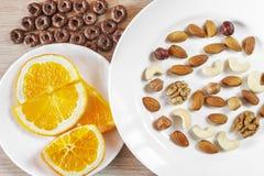 Sortierte Nüsse, orange Scheiben auf weißen Platten, knusprige ganze Korn-Getreide ringsum Hafer auf Holztisch Gesunder organisch stockfotografie