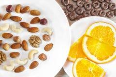 Sortierte Nüsse, orange Scheiben auf weißen Platten, knusprige ganze Korn-Getreide ringsum Hafer auf Holztisch Gesunder organisch lizenzfreie stockbilder
