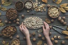 Sortierte Nüsse und Herbstlaub Stockbild