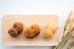 Sortierte Plätzchen auf hölzernen Brettern weißer Hintergrund und Weizen Stockfoto