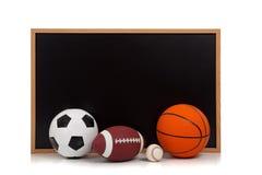 Sortierte Sportkugeln mit einem Tafelhintergrund Stockfoto