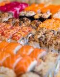 Sortierte Sushi und Rollen auf hölzernem Brett im dunklen Licht Stockfotografie