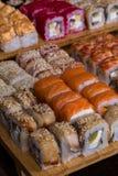 Sortierte Sushi und Rollen auf hölzernem Brett im dunklen Licht Stockbilder