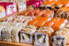 Sortierte Sushi und Rollen auf hölzernem Brett im dunklen Licht Stockbild