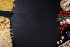 Sortierte Teigwaren mit Eiern, Pilzen und italienischen Küchebestandteilen auf schwarzem Hintergrund Draufsicht, Kopienraum Lizenzfreies Stockfoto