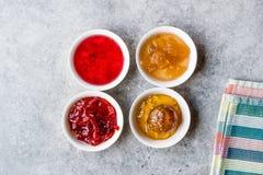 Sortierte Vielzahl von Staus und von Marmeladen; Rose, roter Pfeffer, Mandarine und zitronengelbe Schale in der kleinen Schüssel stockbild