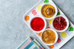Sortierte Vielzahl von Staus und von Marmeladen; Rose, roter Pfeffer, Mandarine und zitronengelbe Schale in der kleinen Schüssel stockfotos