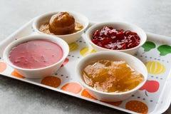 Sortierte Vielzahl von Staus und von Marmeladen; Rose, roter Pfeffer, Mandarine und zitronengelbe Schale in der kleinen Schüssel lizenzfreies stockbild