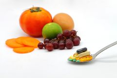 Sortierte Vitamine und Ernährungsergänzungen im Umhüllungslöffel auf buntem Fruchthintergrund der Unschärfe Lizenzfreie Stockbilder
