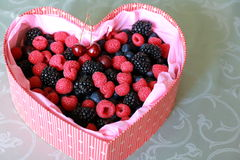 Sortierte wilde Beeren im roten Kasten des Geschenks in Form von Herzen Lizenzfreies Stockfoto