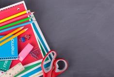Sortierter Schulbedarf auf einem Tafel-Hintergrund Lizenzfreies Stockfoto