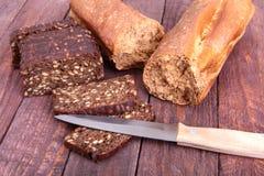 Sortiertes frisches selbst gemachtes Brot und Messer auf hölzernem Hintergrund Selektiver Fokus Stockbild
