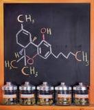 Sortiertes medizinisches Marihuana rüttelt gegen Brett mit THC-Formel Lizenzfreie Stockbilder