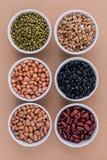 Sortiment av bönor och linser i träskedisolat på vit Royaltyfria Bilder