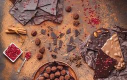 Sortiment av chokladstänger, tryfflar, kryddor och kakaopulver Arkivbilder