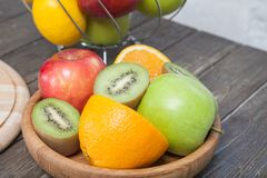 Sortiment av den exotiska fruktnärbilden: kiwi, rött och grönt äpple, apelsiner och citron på trätabellen arkivbild