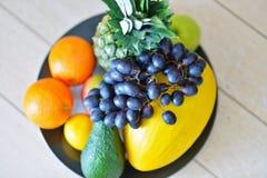 Sortiment av exotiska frukter på trägolvet Royaltyfri Bild