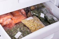 Sortiment av frozenVegetables i hem- kyl Djupfryst mat i kylskåpet arkivfoto