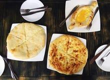 Sortiment av georgian mat, khachapuri Bästa sikt på det traditionella georgian bagerit, olika pajer med ost på trätabellen Royaltyfri Fotografi