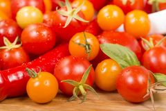 Sortiment av körsbärsröda tomater och peppar royaltyfria bilder
